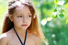 Unhappy little girl. Little girl is thinking or unhappy outdoor in green park Stock Image