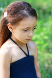 Unhappy little girl. Little girl is thinking or unhappy outdoor in green park Stock Photo