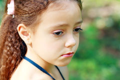 Unhappy little girl. Little girl is thinking or unhappy outdoor in green park Stock Images