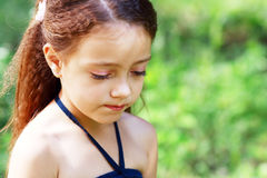Unhappy little girl. Little girl is thinking or unhappy outdoor in green park Royalty Free Stock Photography