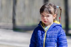 Portrait of a despaired little girl with unhappy expression. Unhappy little girl wearing a blue and yellow coat. annoyed expression Royalty Free Stock Photos
