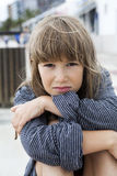 Unhappy little girl wearing striped t-shirt of her father. Sitting on the bench. Problems with parents Royalty Free Stock Photo