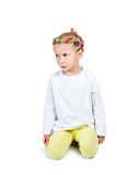 Unhappy little girl. Little girl in a white blouse sits on the floor unhappy isolated on white background Royalty Free Stock Photo