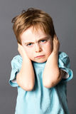 Unhappy little kid disliking his education, protecting his closed ears Royalty Free Stock Image