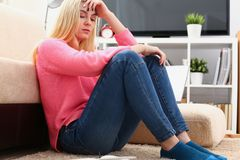 Unhappy lonely depressed woman sitting on the couch stock photo