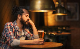 Unhappy lonely man drinking beer at bar or pub Stock Photo