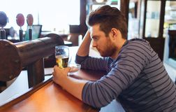 Unhappy lonely man drinking beer at bar or pub Royalty Free Stock Photography