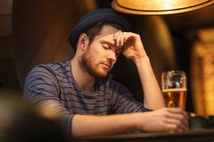 Unhappy lonely man drinking beer at bar or pub Stock Images