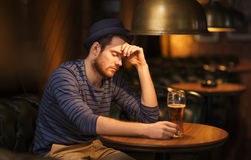 Unhappy lonely man drinking beer at bar or pub Royalty Free Stock Photos