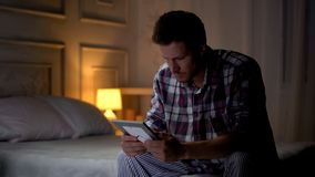 Unhappy lonely young male sitting on bed looking at photo, breakup, missing wife. Stock photo stock photography