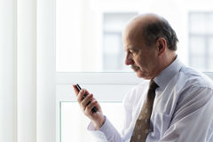 Unhappy looking in smart phone Stock Image