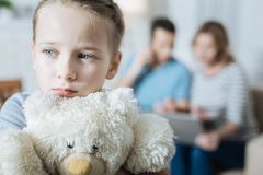 Unhappy little girl hugging her teddy bear. Unhappy. Lovely sad blue-eyed little girl hugging her teddy bear and feeling alone while her parents working on their Royalty Free Stock Photos