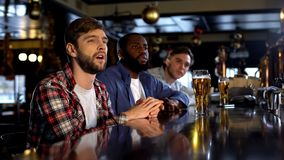 Unhappy male friends watching championship in bar, team losing game, failure. Stock photo stock photo