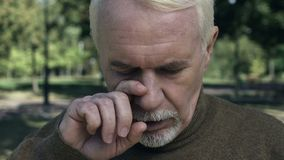 Unhappy male pensioner wiping tears, nostalgia memories, grief emotions, problem