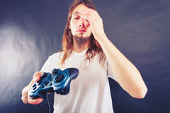 Unhappy male playing games Stock Images