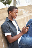 Unhappy Male Teenage Student Sitting Outside. On College Steps Using Mobile Phone Royalty Free Stock Photography