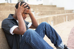 Unhappy Male Teenage Student Sitting Outside Stock Photo