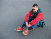 Unhappy Man. Sitting on the ground with room for copyspace Stock Image