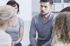 Unhappy man during addiction therapy. Unhappy young men sitting with other people during addiction therapy Royalty Free Stock Image