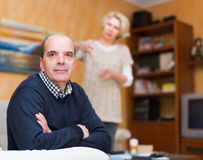 Unhappy man with angry wife. Family quarrel. Unhappy elderly men with angry wife at home Royalty Free Stock Photo