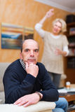Unhappy man with angry wife. Family quarrel. Unhappy senior men with angry mature wife at home Stock Photography