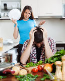 Unhappy man with angry wife at home kitchen. Family quarrel. Unhappy men with angry wife at home kitchen. Focus on girl Stock Images