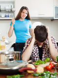 Unhappy  man with angry wife at home. Unhappy young men with angry wife at home. Focus on girl Royalty Free Stock Photo