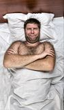 Unhappy man in bed with crossed hands. Top view of unhappy man with crossed hands in white bed stock images