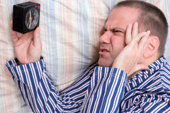 Unhappy man in bed. Man lying in bed with alarm clock Royalty Free Stock Images