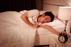 Unhappy man being awakened by an alarm clock in his bedroom in m. Unhappy man being awakened by an alarm clock in his bedroom in the morning Royalty Free Stock Images