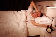 Unhappy man being awakened by an alarm clock in his bedroom in m Stock Images