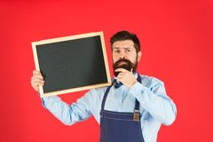 Unhappy man chef with blank blackboard, copy space. bearded hipster cook in apron. great cuisine. cooking by recipe royalty free stock photos
