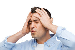 Unhappy man with closed eyes touching his forehead Stock Photo