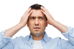 Unhappy man with closed eyes touching his forehead Royalty Free Stock Photo