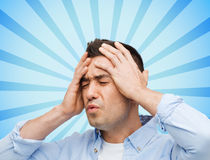Unhappy man with closed eyes touching his forehead Royalty Free Stock Photos