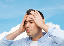 Unhappy man with closed eyes touching his forehead Royalty Free Stock Images