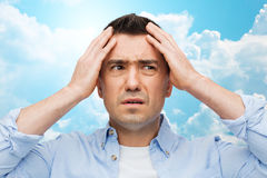 Unhappy man with closed eyes touching his forehead Stock Images