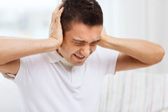 Unhappy man closing his ears by hands at home Royalty Free Stock Photography