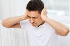 Unhappy man closing his ears by hands at home Stock Photo