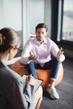 Unhappy man consulting counselor. Unhappy men consulting counselor during therapy stock image