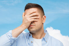 Unhappy man covering his eyes by hand Stock Image