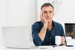 Unhappy Man At The Desk. Portrait Of A Worried Mature Man With Laptop Holding Cup Royalty Free Stock Photo