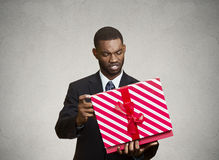 Unhappy man, displeased with new gift. Closeup portrait grumpy, unhappy, upset man holding box, displeased with received gift, disgust on face, isolated grey Stock Photo
