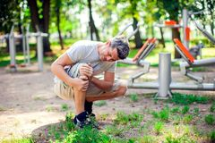 A man feeling pain in his knee during sport and workout in the p royalty free stock image