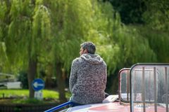 Unhappy man in gray jumper sat on front of barge with blue one way sign in background. Retired lonely man sat on bow of boat wearing grey jumper with gray hair royalty free stock images
