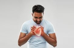 Unhappy man having heart attack or heartache. People, healthcare and health problem concept - unhappy man having heart attack or heartache over grey background royalty free stock photography