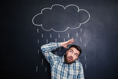 Unhappy man hiding from rain drawn on blackboard background. Unhappy young man hiding from raincloud and rain drawn over him on a blackboard background Stock Image