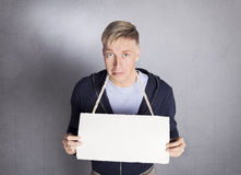 Unhappy man holding empty signboard. Stock Image
