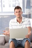 Unhappy man with laptop at home Stock Photo