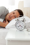 Unhappy man looking at his alarm clock Royalty Free Stock Photo